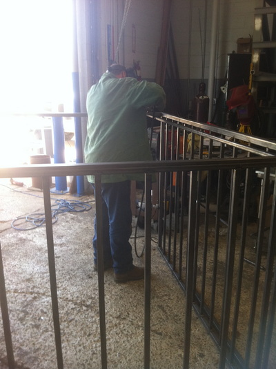Worker welding anti-theft cage for HVAC components