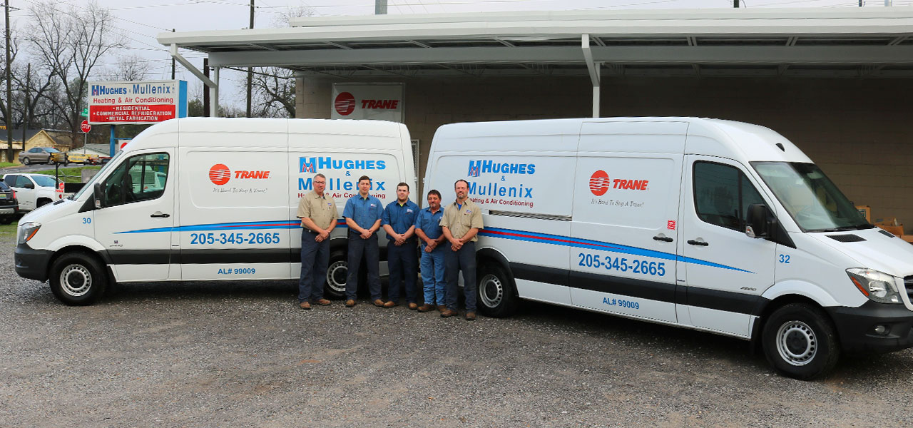 Hughes & Mullenix employees in front of vans